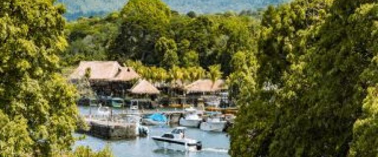 un esceno de un lago con barcos y un volcan